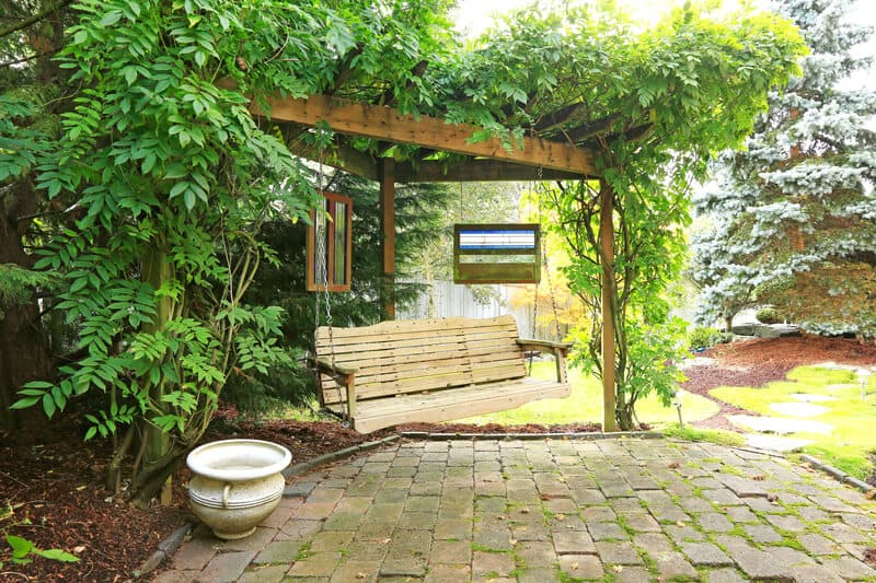 Summer backyard garden with rest area. View of wooden hangin bench and brich floor.
