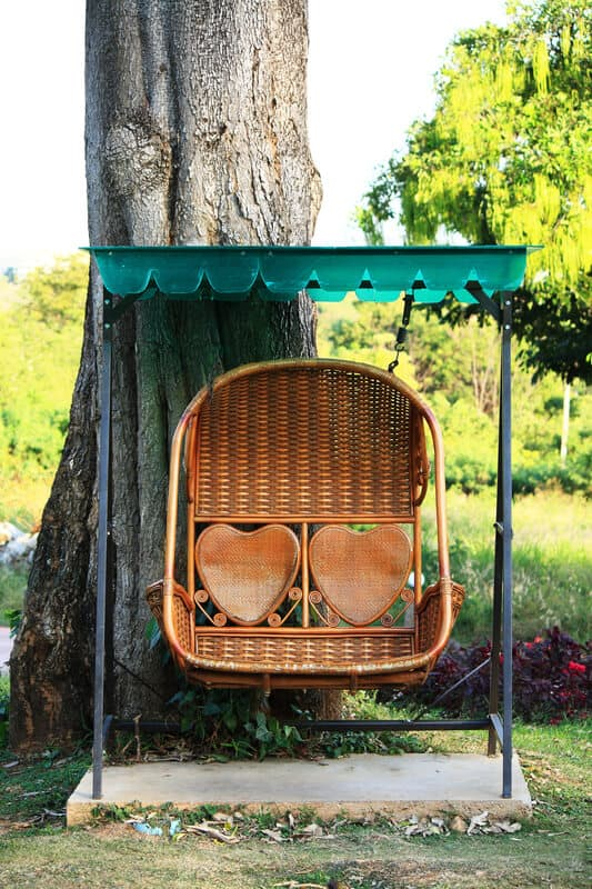 Rattan swing bench in garden with couple of heart shape decoration.