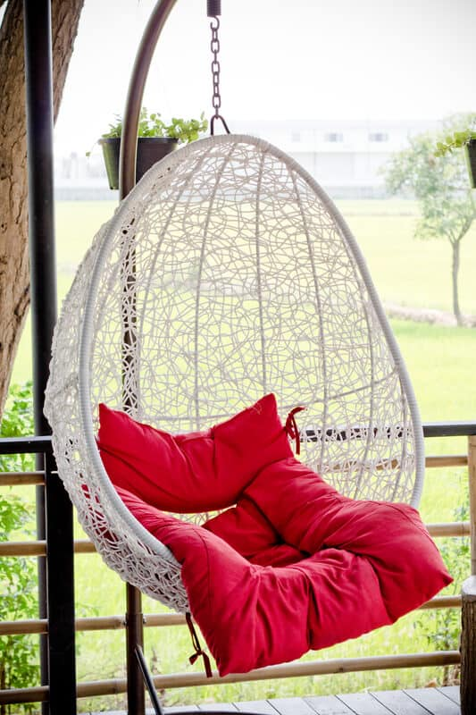 Vintage hanging chair with red seat.