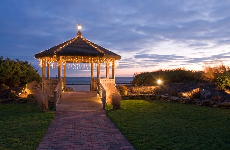A romantic view of a beachfront gazebo with decorative strings of light at the end of a fading sunset.