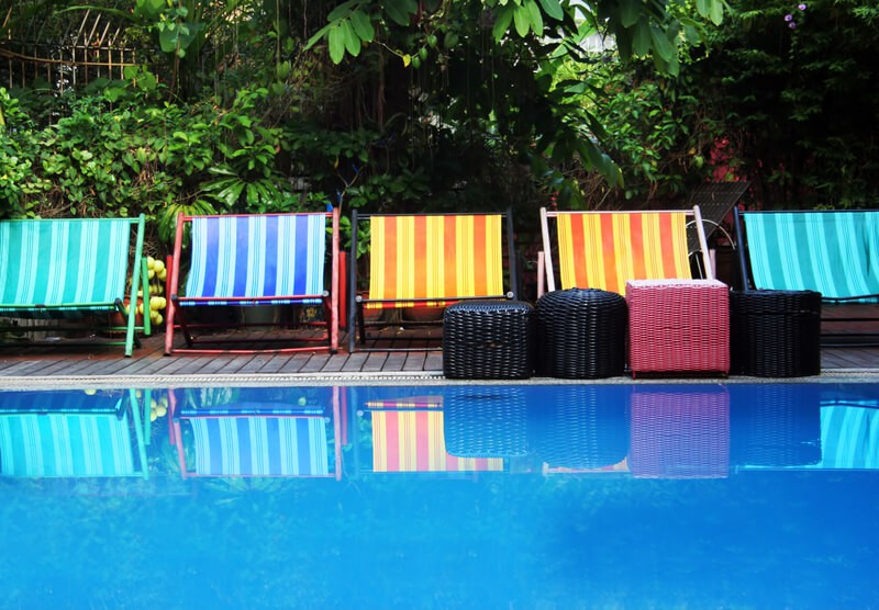 Deck chair and furniture next to a swimming pool.