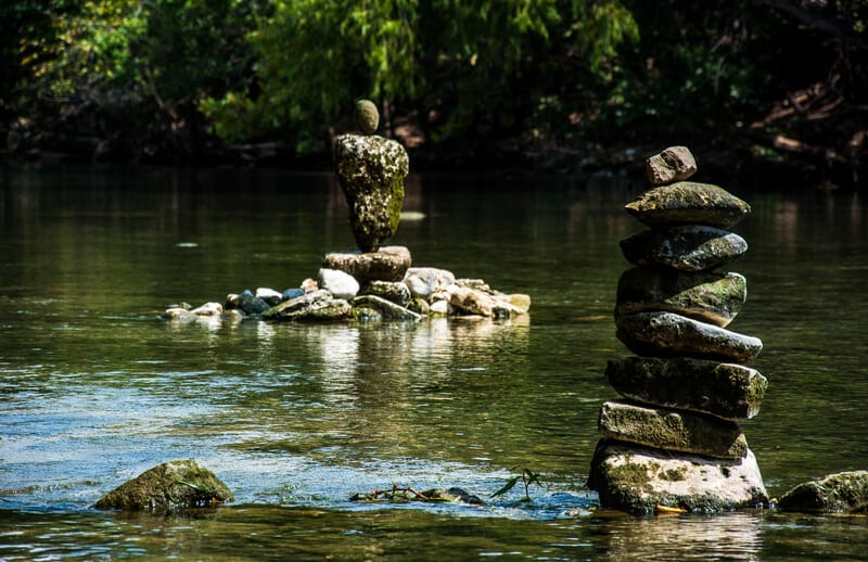 Rock Stacking Zen Formation in river in the barton springs pool area of Austin , Texas. Right off of the colorado river stacking rocks for a tranquil calm relaxing meditation Rock Stacking