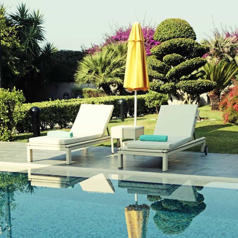 White outdoor furniture and yellow umbrella near the swimming pool for relax on summer resort