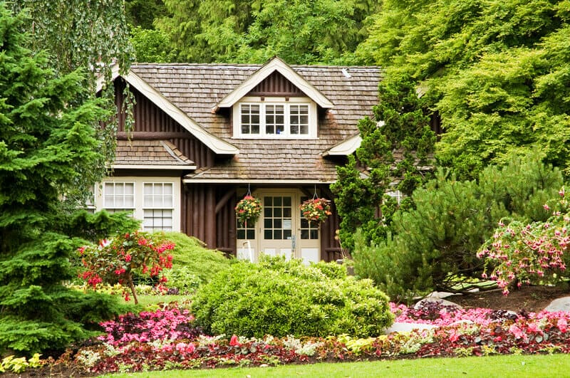 A view of a small log cottage secluded in the woods with colorful flower landscaping. A cozy log cottage is beautifully adorned with greenery of all shapes and sizes.
