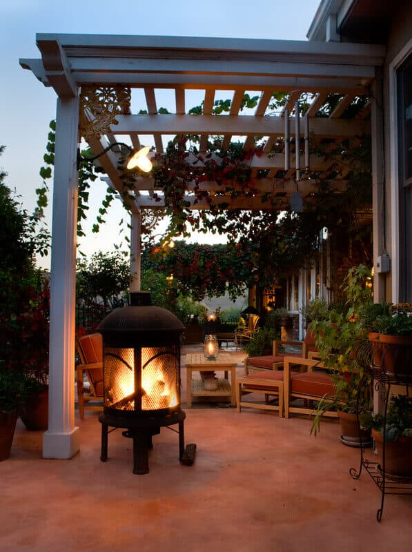 An outdoor patio with fireplace. This comfortable patio features a fully functioning outdoor fireplace. There are also seats and a table so that the owners of the home can gather around and enjoy it.
