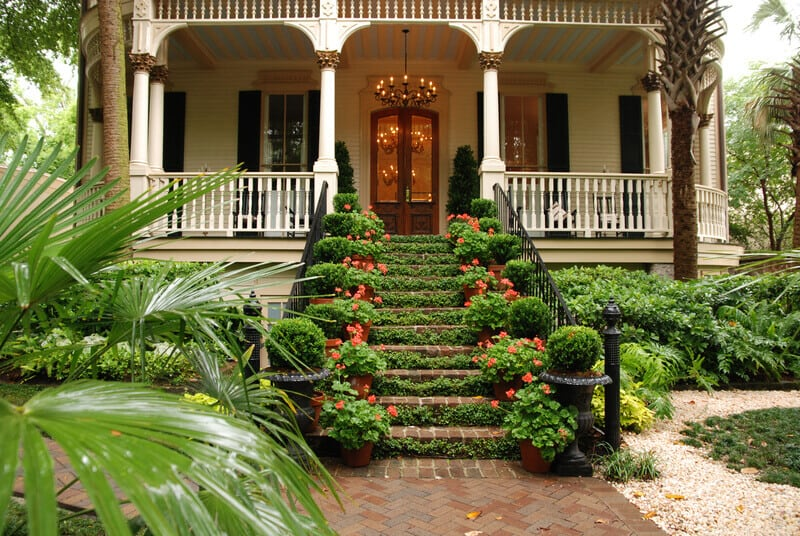 Beautiful front stairs and yard of historic colonial home with flowers and ivy.