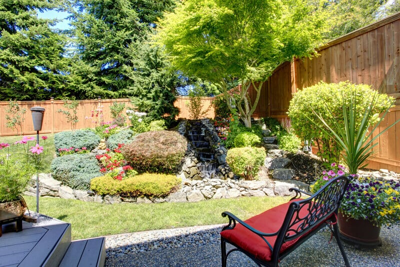 Beautiful landscape design for backyard garden with small bench. This asymmertical backyard design has a wealth of creative ideas applied to it. Notice the seat in the shade, keeping visitors away from the sun's heat.