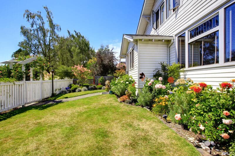 Front yard landscape with flowers and white fence. This front yard is all about the bare necessities, but the owner still maintains a wonderful outer appearance.