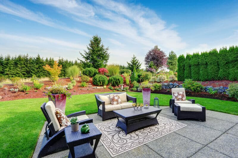 Impressive backyard landscape design. Cozy patio area with settees and table. This outdoor patio is a stunning addition to any backyard design. The grey tiles match nicely with the dark brown outdoor furniture.