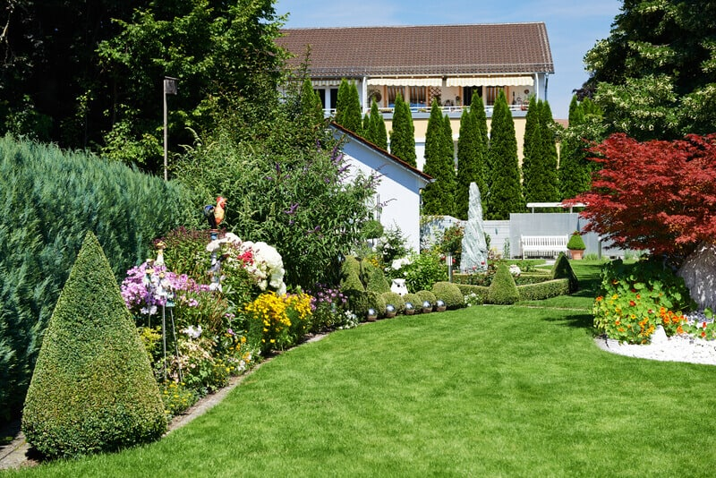 Landscape design. Garden with green grass and flowers near cottage. When you trying to think of more DIY backyard ideas to try, take a chance to think outside the box – by using curves!