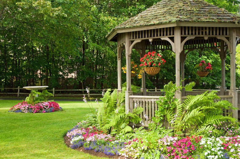 Landscaping around a gazebo with hanging flower baskets in a quiet park. Adding a gazebo to your outdoor space allows you to observe the beauty of your yard from a comfortable sitting place.