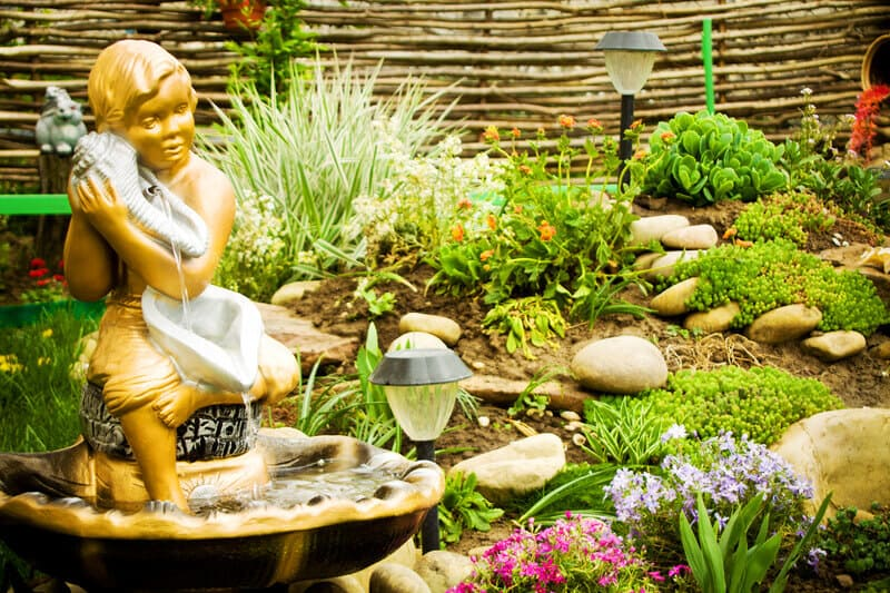 Lanscape design of home garden. Mix up your garden design with fountains, stones and lanterns. This home garden scene uses a mix of all three against a background of a brown fence made with thin, long pieces of wood, adding a bit of a rustic feel.