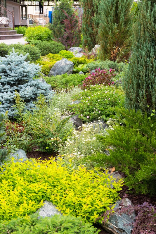 Natural stone landscaping in home garden. Try using taller trees and shrubs to enhance your area. You can also enhance your environemnt large stones places in specific, spaced-out areas.