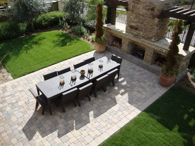 Beautiful outdoor patio with a fireplace and a table and chairs. This is a large outdoor backyard decoration with dinner tables included.