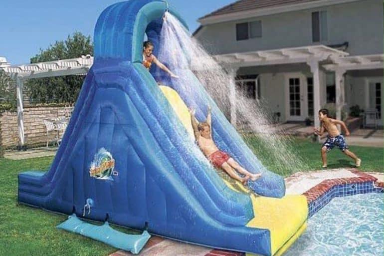 kid sliding down an inflatable banzai water slide