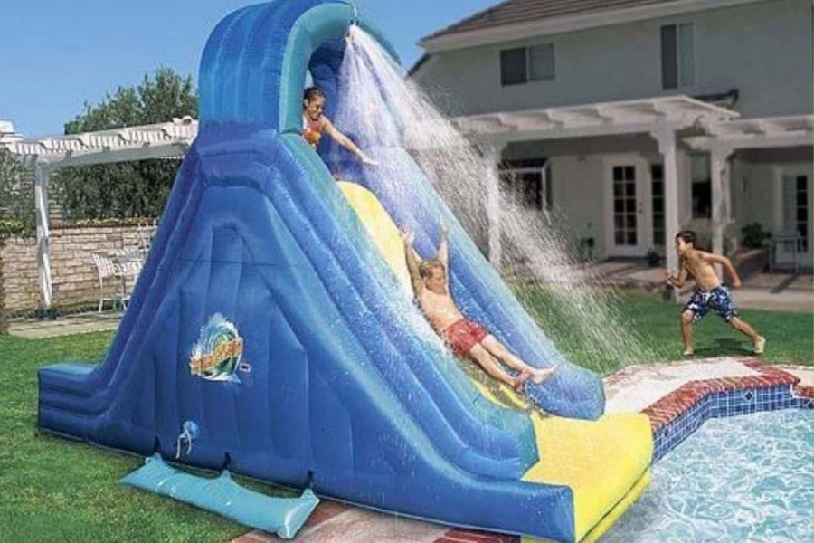 kid sliding down an inflatable banzai water slide